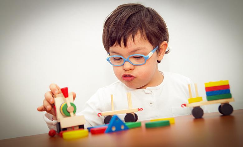 NIño de tres años con discapacidad jugando con un tren.
